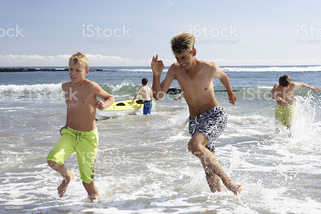 Teenagers playing on beach royalty-free stock photo