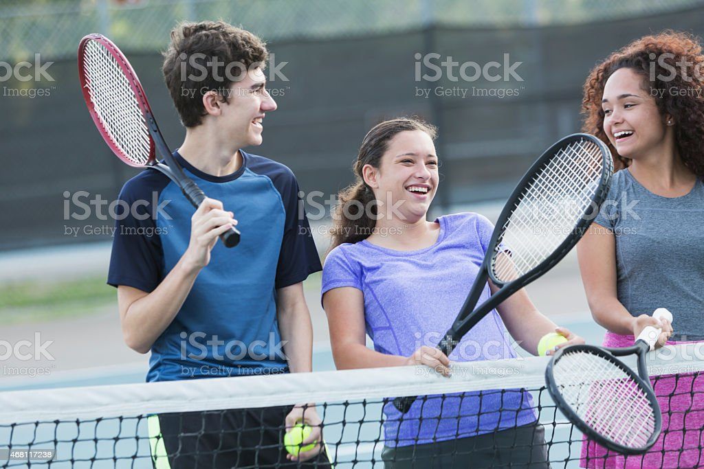 Teenagers playing tennis stock photo