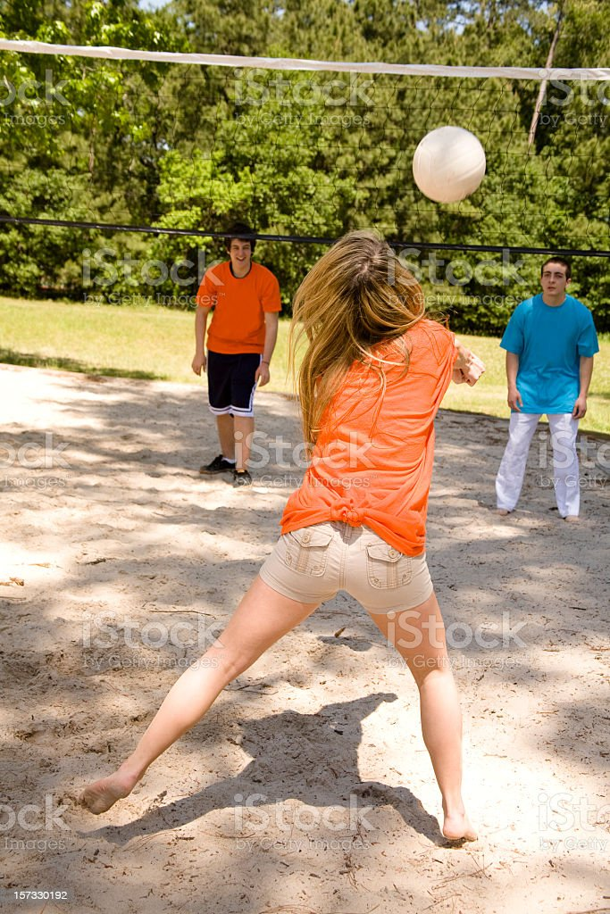 Teenagers playing volleyball in the summer stock photo