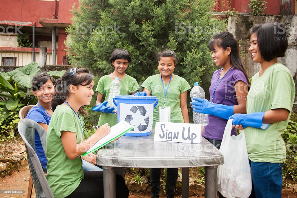 Teenagers register at recycling volunteer check-in table. Multi-ethnic group. stock photo