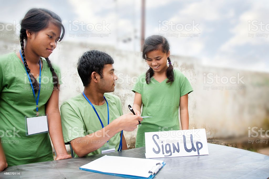 Teenagers register at volunteer check-in table. Multi-ethnic group. stock photo