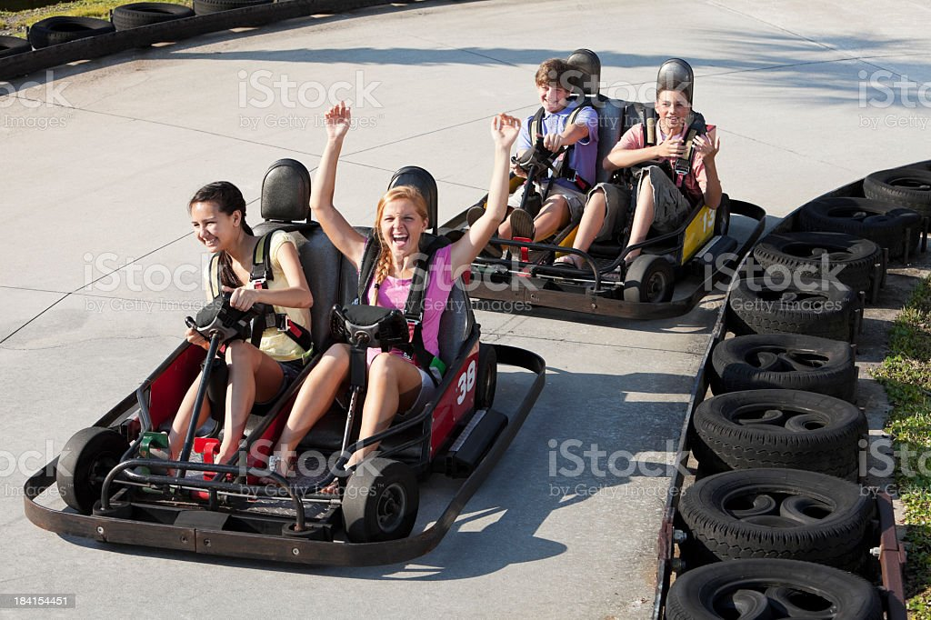 Teenagers riding go-carts stock photo