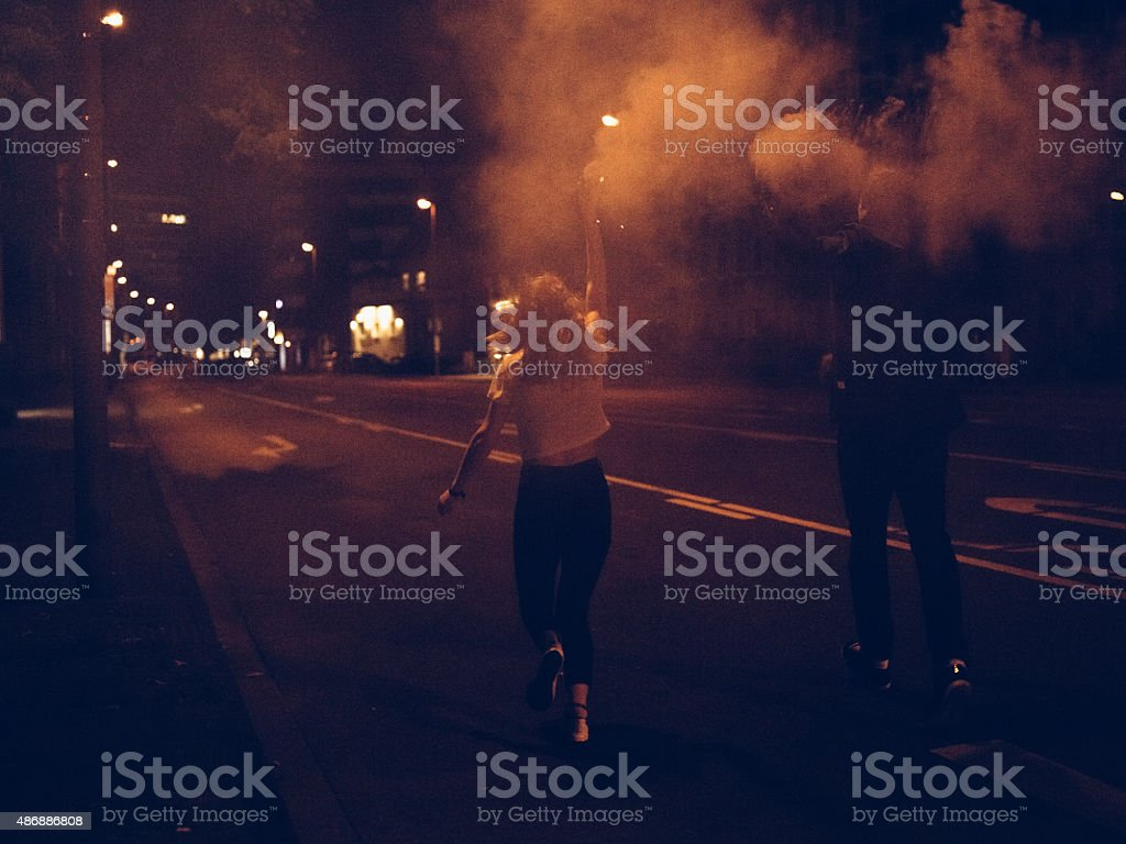 Teenagers running down city street with smoke flares at night stock photo