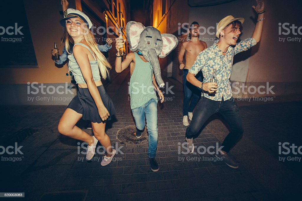 Teenagers Running Down Street During Night Party stock photo