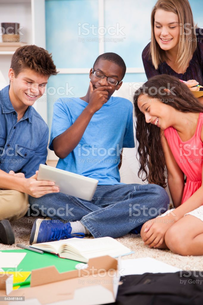 Teenagers share social media, homework on digital tablet at home. stock photo