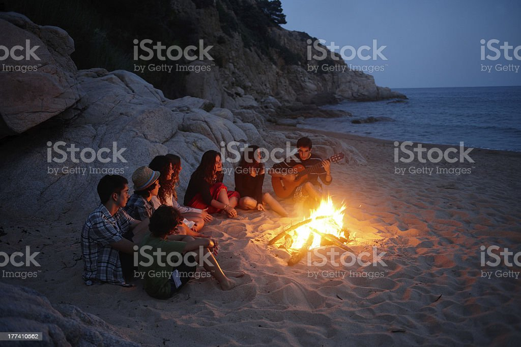 teenagers singing around a fire in the beach stock photo