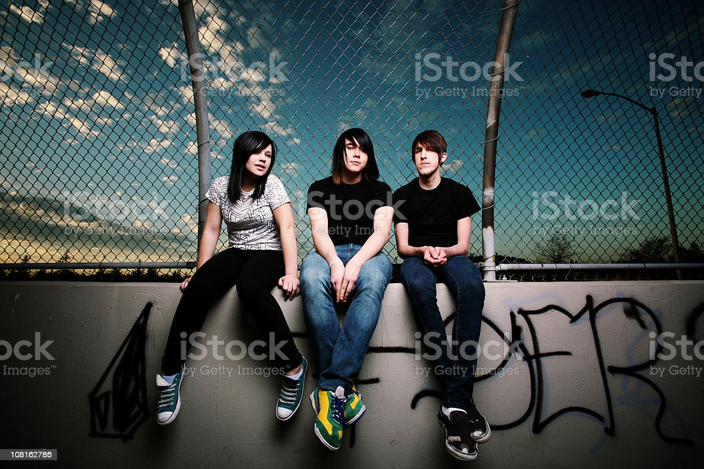 Teenagers Sitting by a Fence royalty-free stock photo