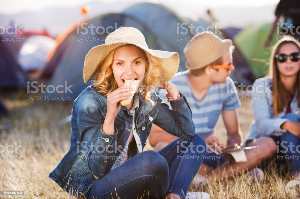 Teenagers sitting on the ground in front of tents and eating stock photo