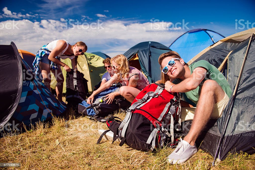 Teenagers sitting on the ground in front of tents stock photo