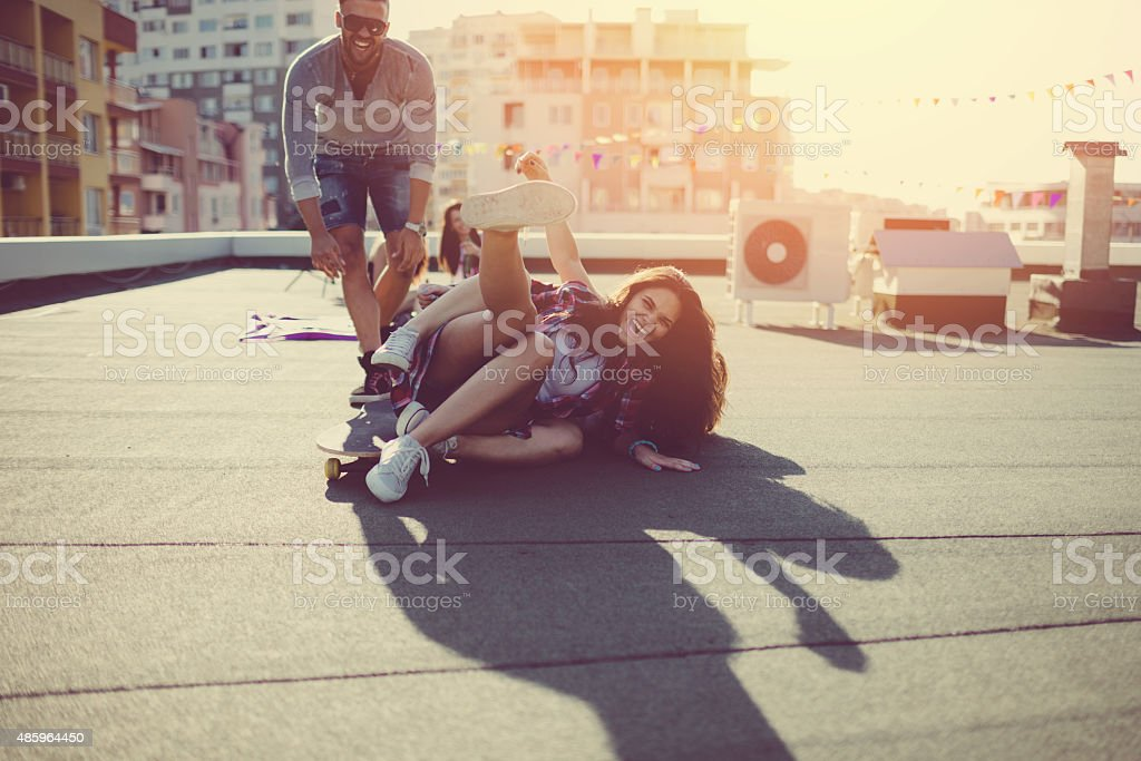 Teenagers skateboarding on the rooftop stock photo