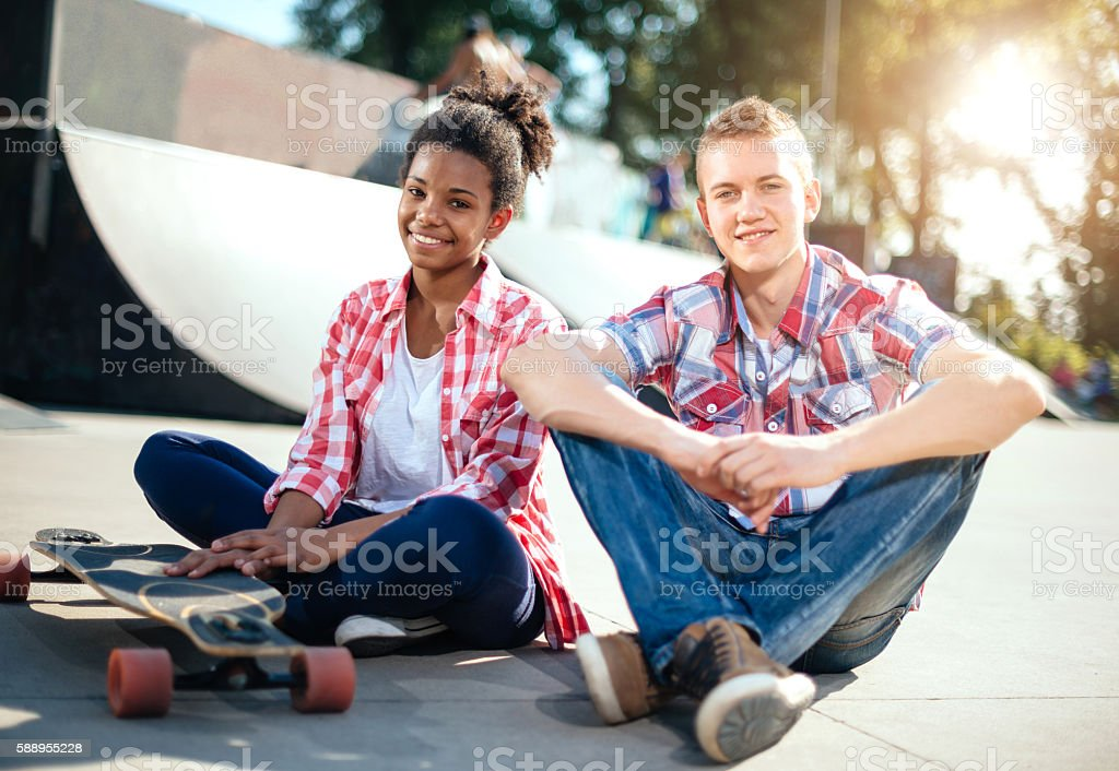 Teenagers spending afternoon in skate park stock photo