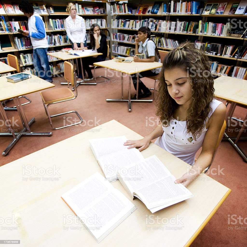 Teenagers studying in a library royalty-free stock photo