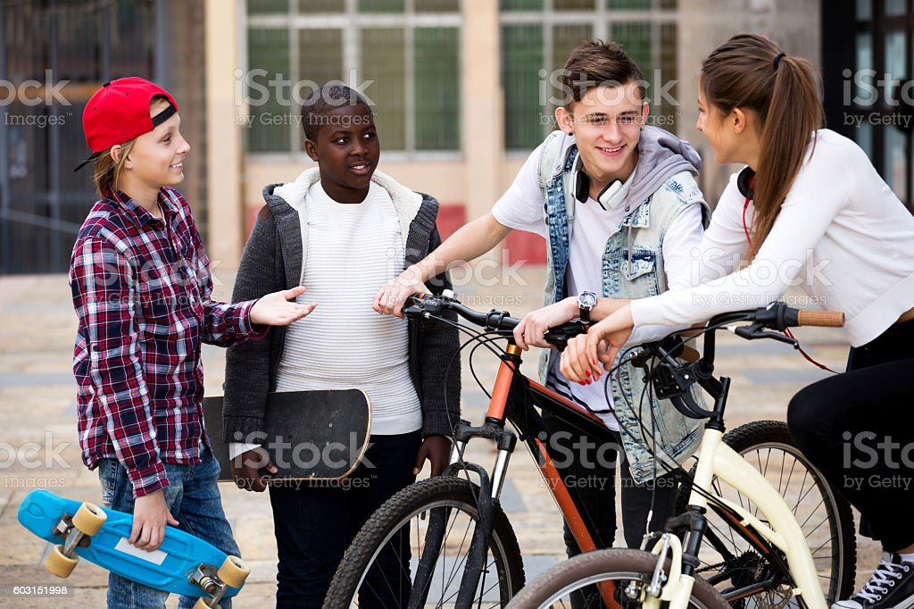 Teenagers with skateboards posing in town square stock photo