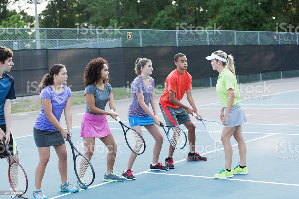 Teenagers with tennis coach doing drills stock photo