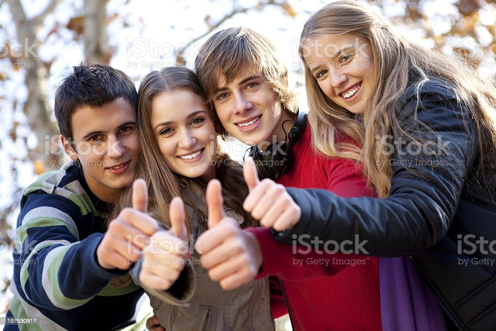 Teenagers with their thumbs up and standing outside royalty-free stock photo