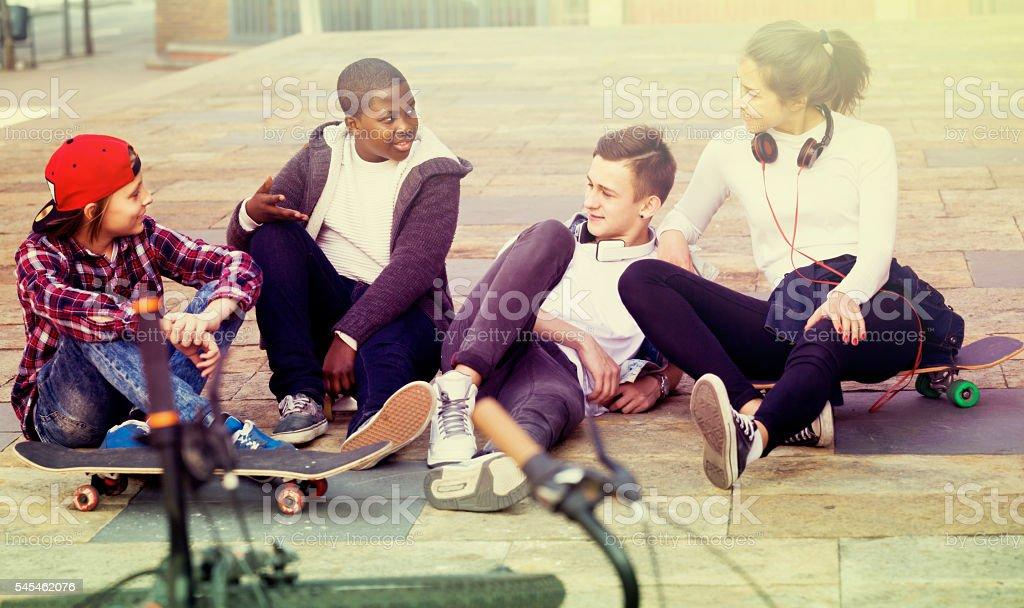 teens chatting near bikes stock photo