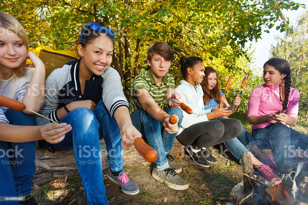 Teens grilling sausages sitting near yellow tent stock photo