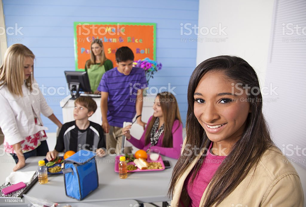 Teens in school cafeteria eating lunch.  Menu on wall royalty-free stock photo