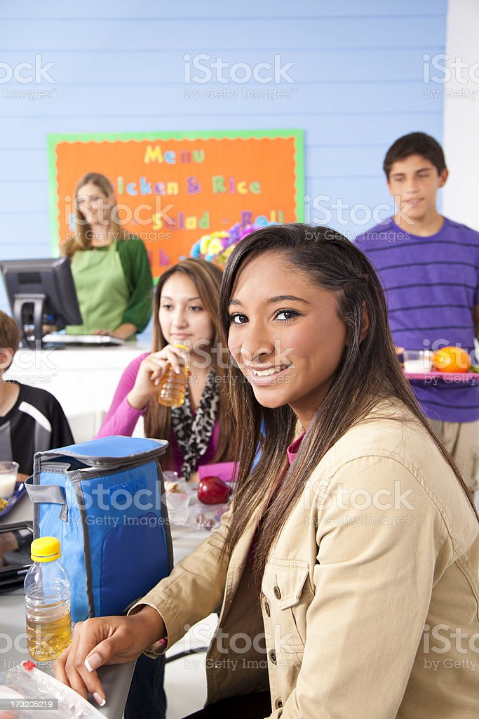 Teens in school cafeteria eating lunch.  Menu on wall. royalty-free stock photo