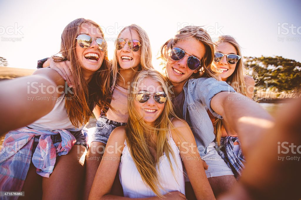 Teens in shades taking a group selfie outdoors stock photo