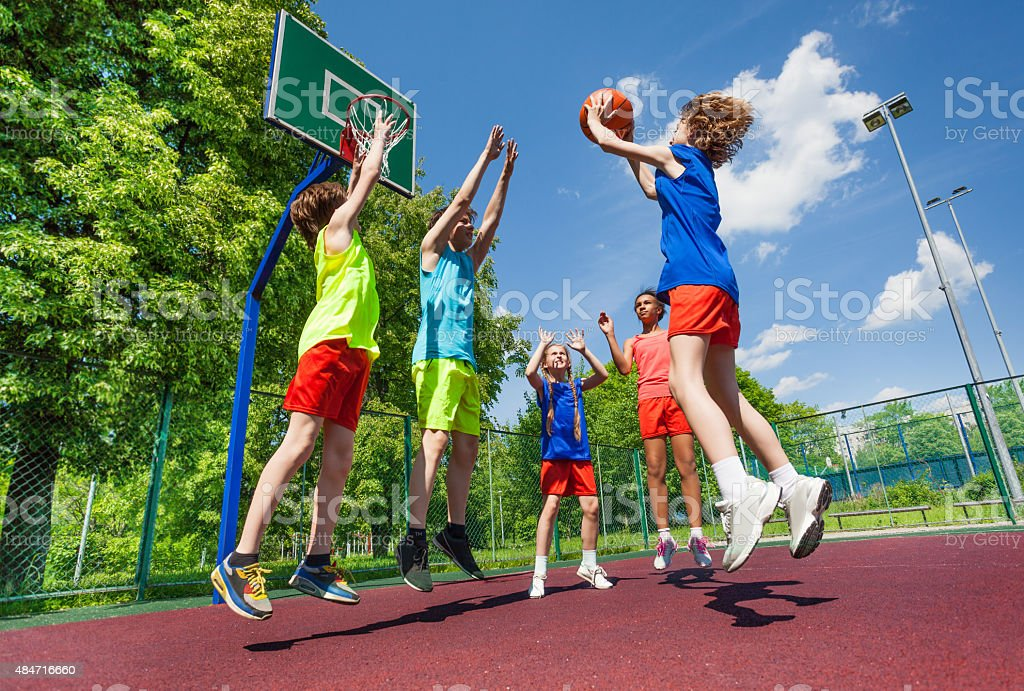 Teens jump for ball during basketball game stock photo