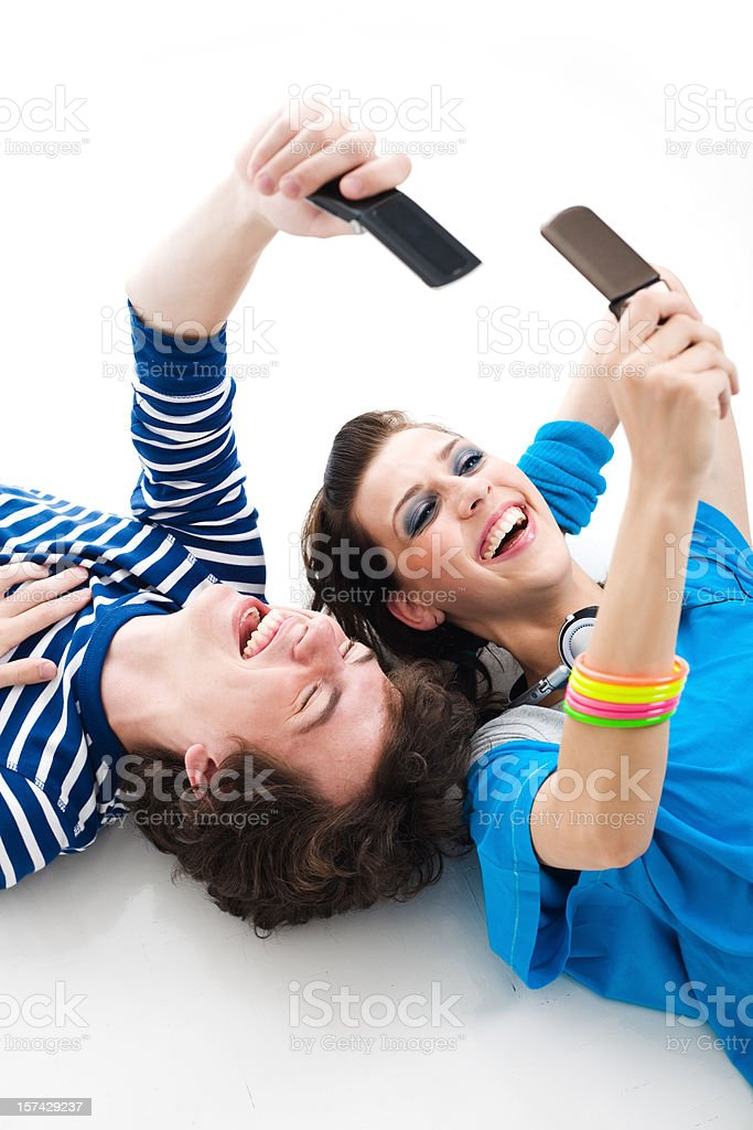 Teens Lying Down And Texting Together royalty-free stock photo