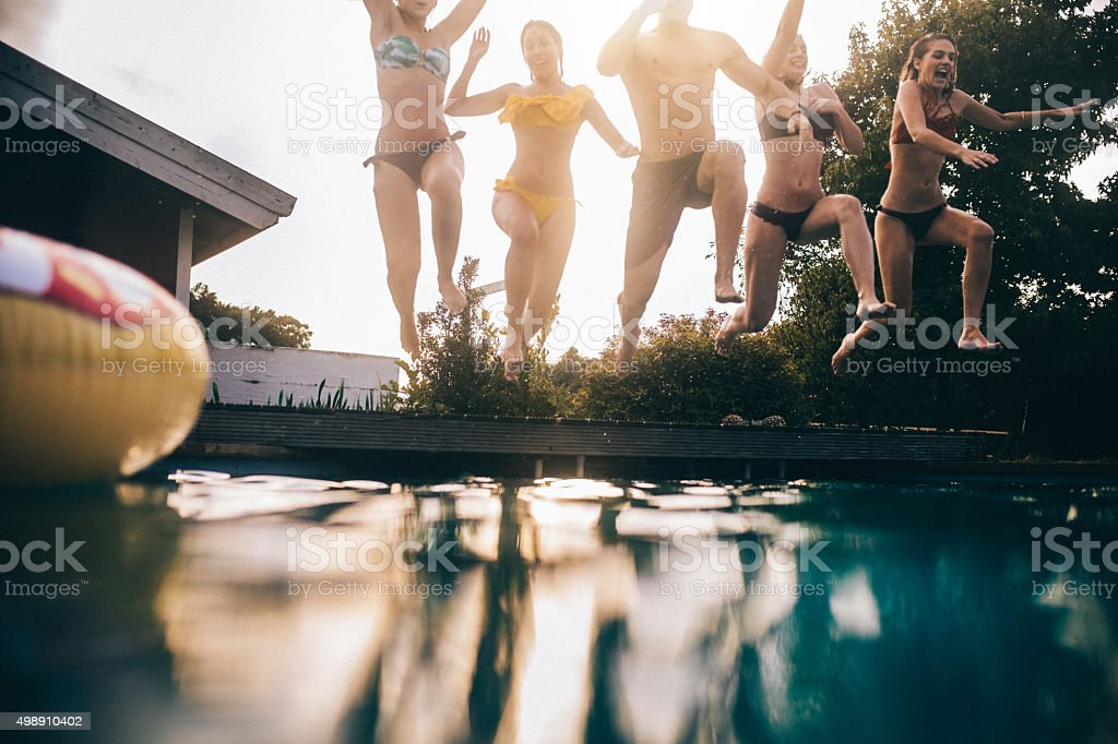 Teens mid-air while jumping into a still swimming pool stock photo