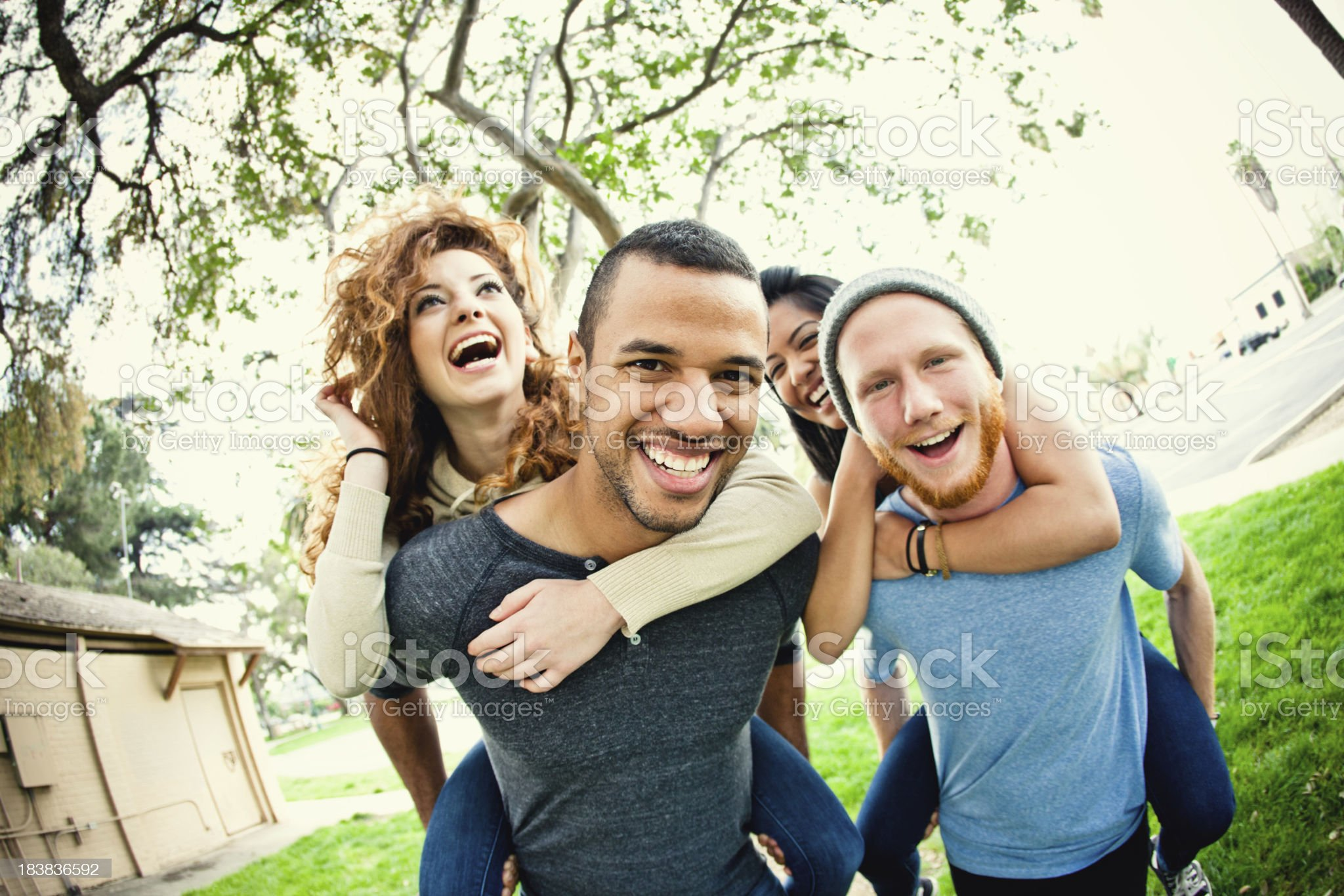 Teens running and girls on the boys backs laughing royalty-free stock photo