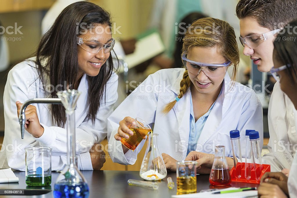 Teens using chemistry set during high school science experiement stock photo