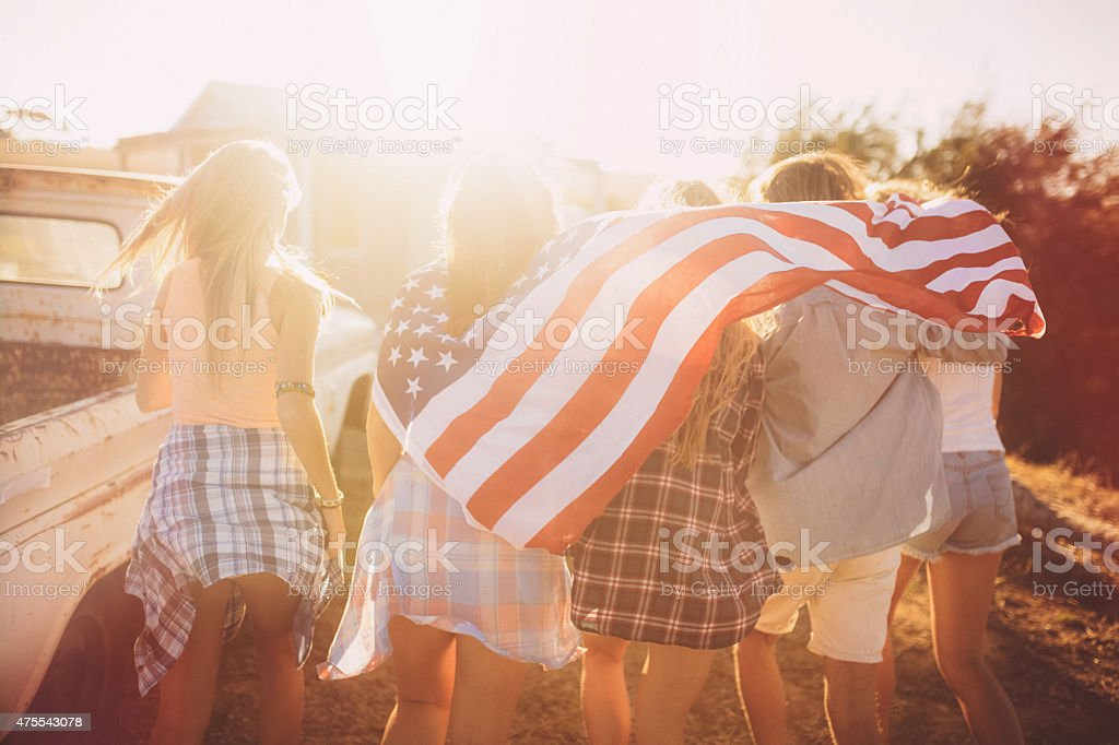 Teens walking with an American flag in sun flare stock photo