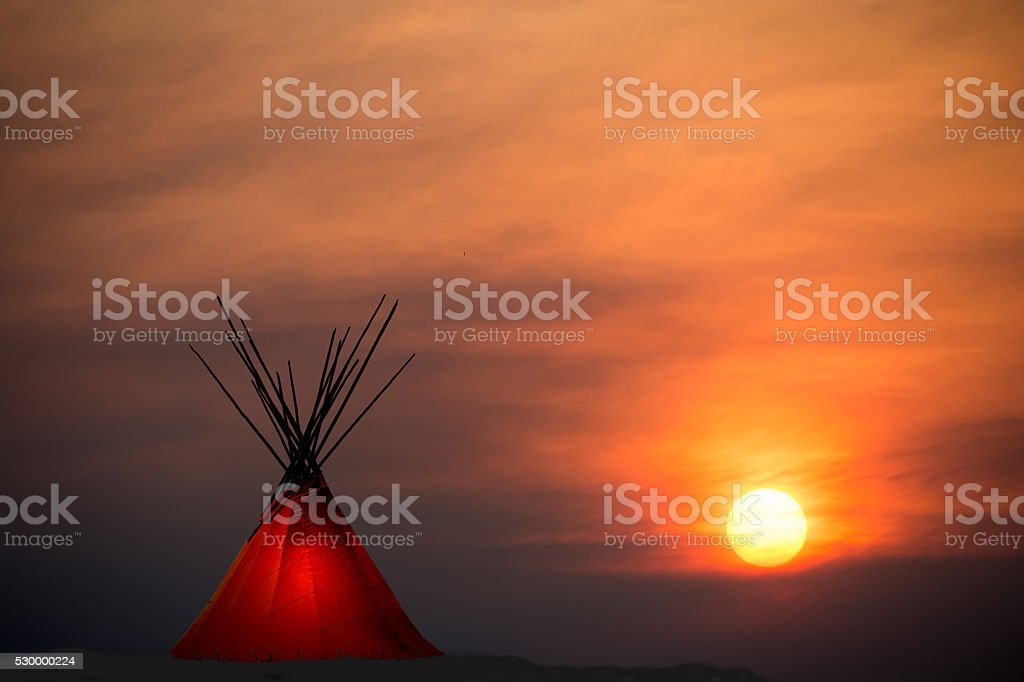 Teepee and gold, dark,  sunset- light in teepee- copy space stock photo
