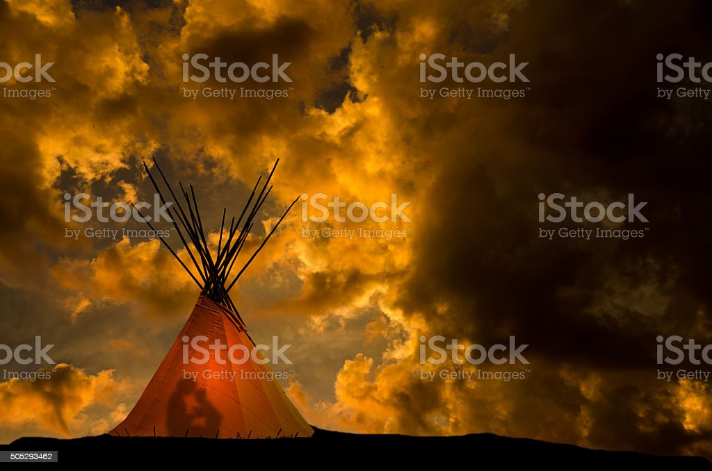 Teepee and gold sunset- light and people in the teepee stock photo