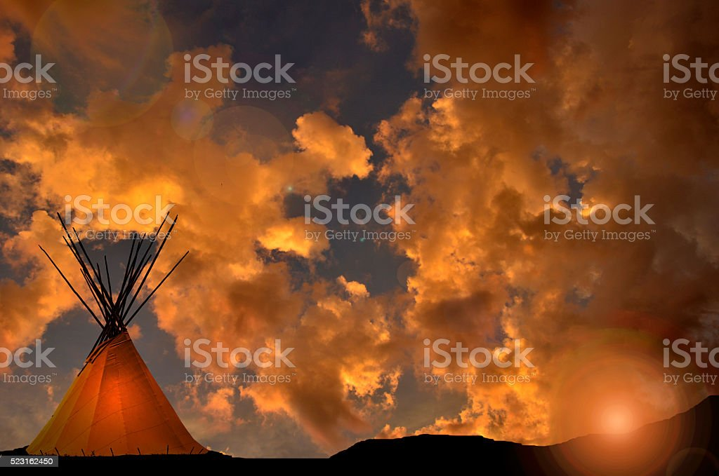 Teepee at sunset with gold and orange dramatic sky stock photo