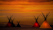 Teepee camp and gold, dark,  sunset- light in teepees