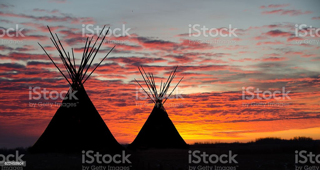 Teepee camp and gold, dark,  sunset- two stock photo