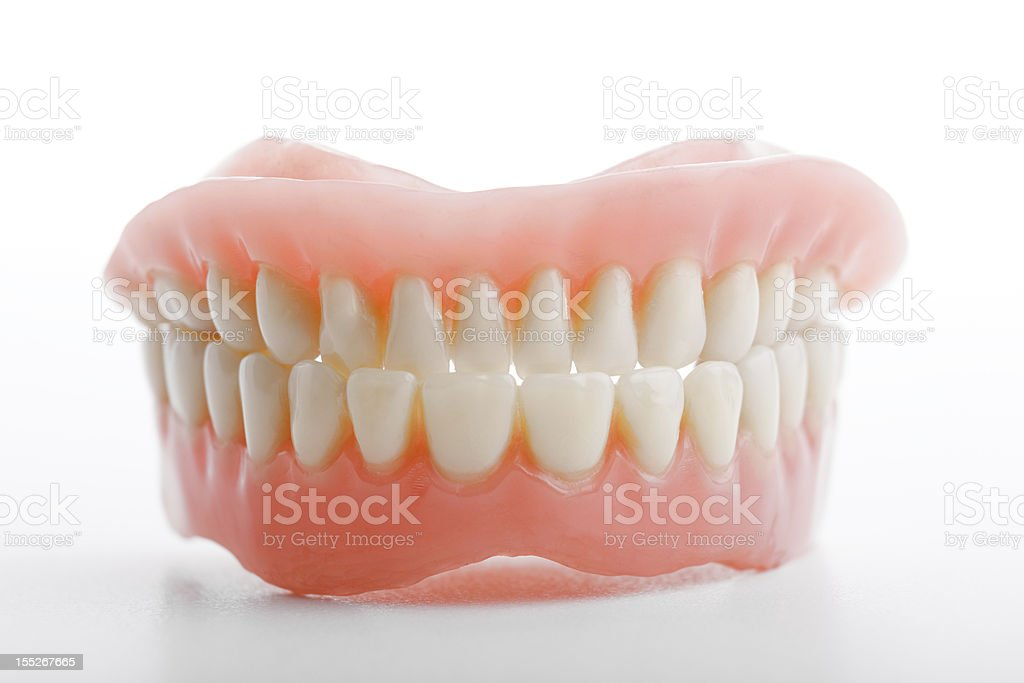 Teeth prosthetics upside down against white background stock photo