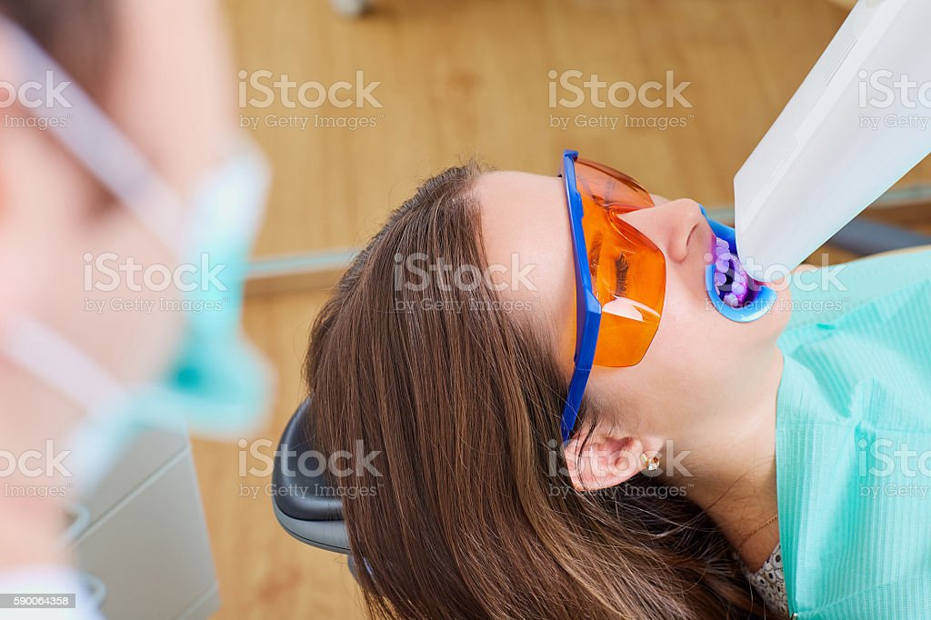 Teeth whitening lamp ultravioleta. The girl on reception at stock photo