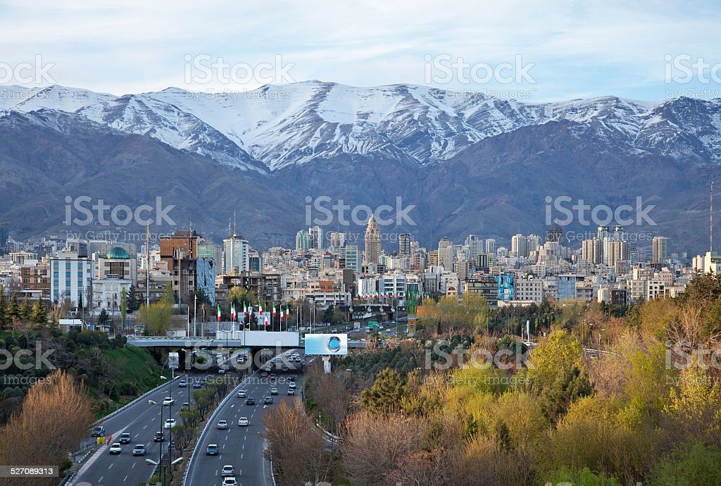 Tehran Skyline and Highway in Front of Snowy Mountains stock photo