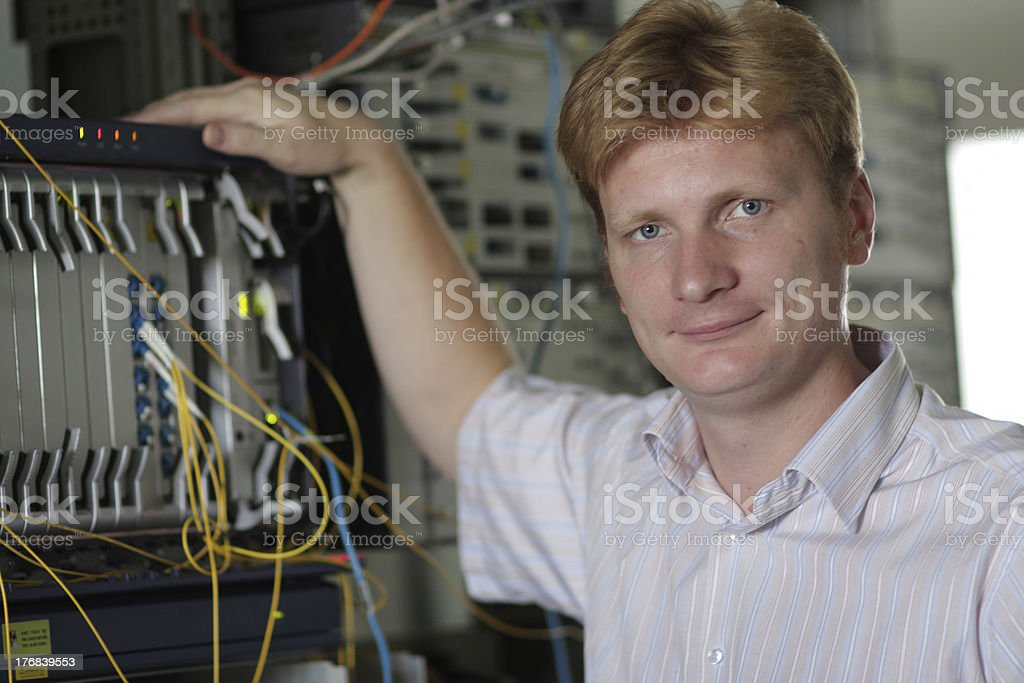 Telecom engineer poses on multiplexer background royalty-free stock photo