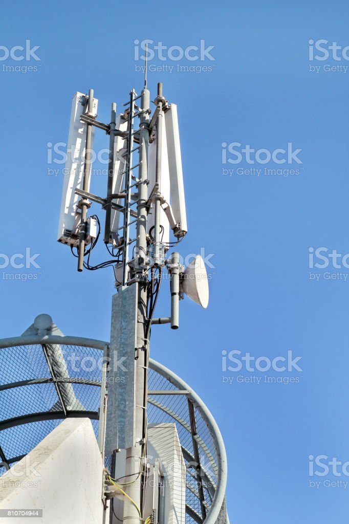 Telecommunication base stations network repeaters. The cellular communication aerial on a building. Communications cell phone telecommunication tower. Antenna tower and repeater. Modern technology. stock photo