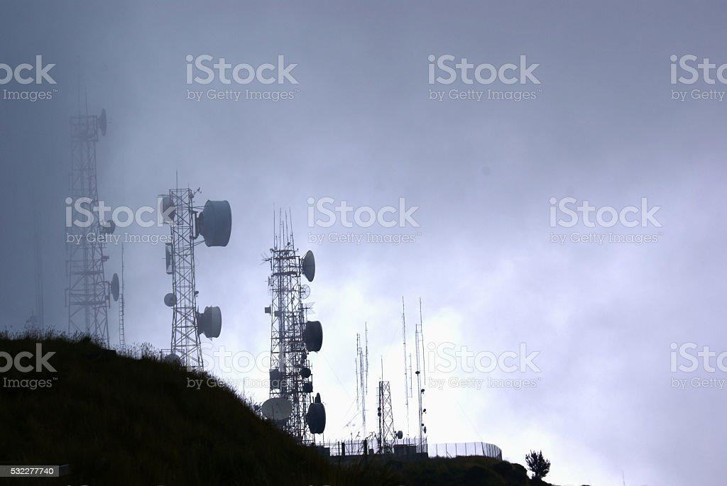 Telecommunication towers in fog stock photo