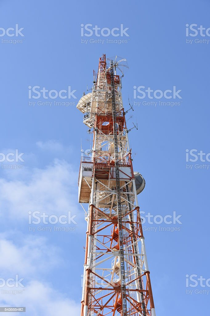 Telecommunications tower against blue sky stock photo