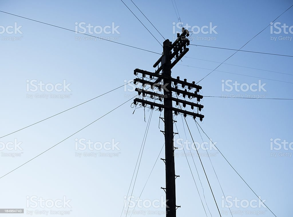 Telegraph Pole Silhouetted on Sky stock photo
