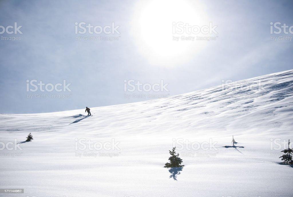 Telemark Skier Making Turn in Scenic Mountain Winter Landscape stock photo