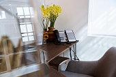 Telephone and flower vase on office desk