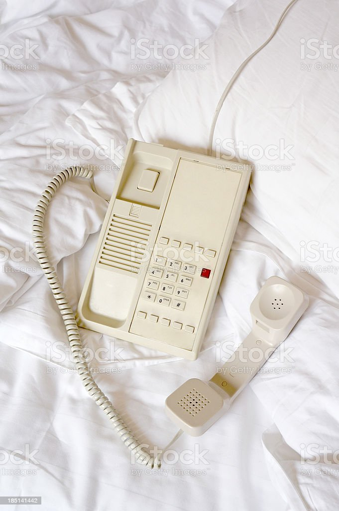Telephone on bed sheet royalty-free stock photo