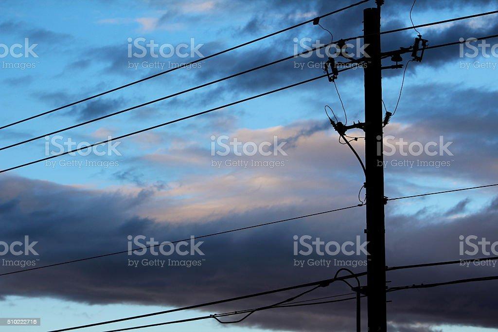 Telephone Pole Silhouette Against Dramatic Sky stock photo