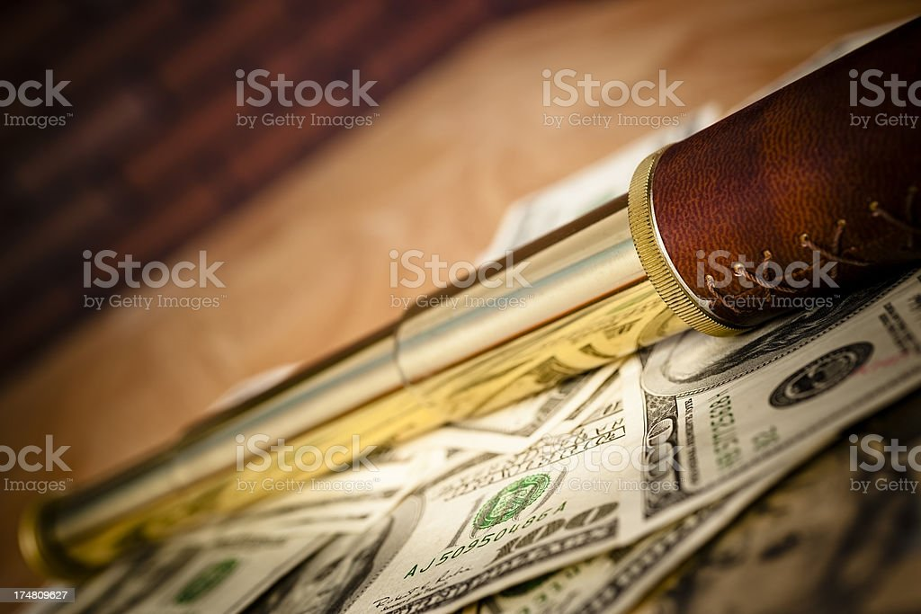 Telescope amid pile of $100 US dollar bills table angled royalty-free stock photo