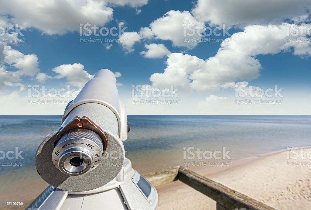 Telescope on a beach pointed at beautiful sky. stock photo