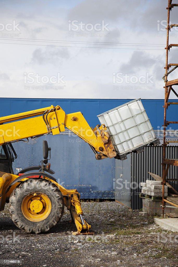 Telescopic handler vehicle lifting a heavy object royalty-free stock photo